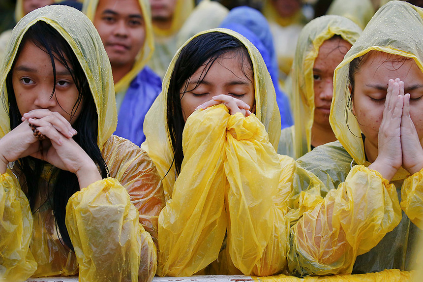 Pilgrims pray as they listen Pope Francis speaking during a mass at Tacloban's airport January 17, 2015. An emotional Pope Francis, wearing a plastic poncho over his vestments to protect him from the wind and rain on Saturday, comforted survivors of Typhoon Haiyan, the Philippines' worst natural disaster that killed about 6,300 people 14 months ago.   REUTERS/Damir Sagolj (PHILIPPINES)
