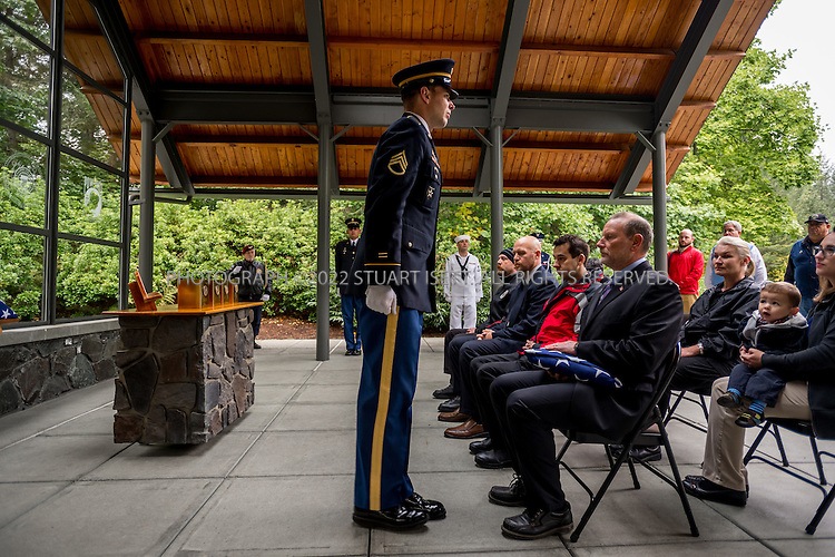 9/30/2016-- Tahoma National Cemetery, Kent, WA, USA<br /> <br /> Here: Tom Yokes (seated), a US Coast Guard veteran, volunteers to accept a flag on behalf of deceased veteran Russell Ristow, in a commitment shelter at the Tahoma National Cemetery.<br /> <br /> James Lindley, 34, an undertaker and US Marine Corp Veteran, works at the Columbia Funeral Home in Seattle, Washington and has taken it upon himself to process the remains of indigent veterans and ensure their remains are placed in Tahoma National Cemetery in nearby Kent, WASH. The veterans are given full military funerals with active service members as well as volunteers who stand-in for unavailable next-of-kin, accepting the folded flags provided by the Veterans Administration.<br /> <br /> On this day, with the help of Mr. Lindley, the remains of 4 veterans were interred at the Tahoma National Cemetery: <br /> <br /> Richard Fesler, born 1951, died 2014. US Army Veteran<br /> Rocky Stallone, born 1951, died 2014. Marine Corps veteran<br /> Russell Ristow, born 1944, died 2014. US Army veteran.<br /> Wayne Roberts, Born 1937, died 2014. US Navy veteran.<br /> <br /> <br /> Credit: Stuart Isett for The Wall Street Journal. <br /> VETBODIES<br /> <br /> &copy;2016 Stuart Isett. All rights reserved.