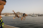Boys dives from a pier into the water of Sultan Qaboos Port in Muscat, Oman.