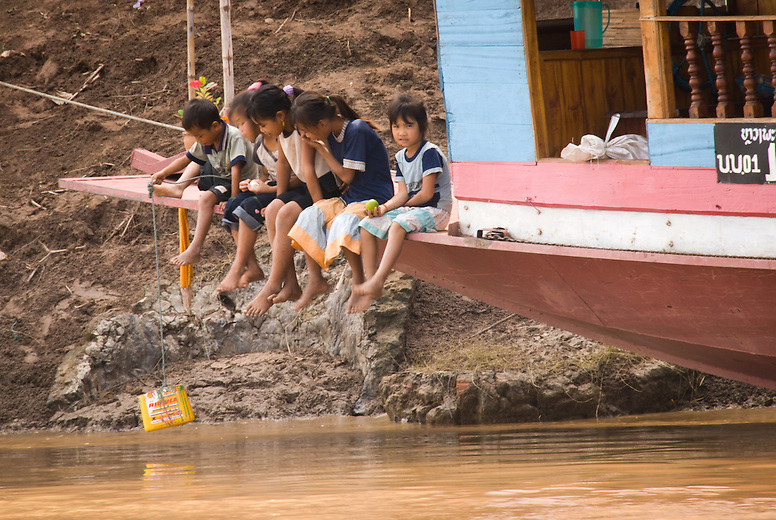 Young children sit on a boat in the Nam Khan river in Luang Prabang, Laos.  Luang Prabang, the former royal capital is situated on a peninsula formed by the Mekong River and the Nam Khan or Khan River and is surrounded by limestone hills.
