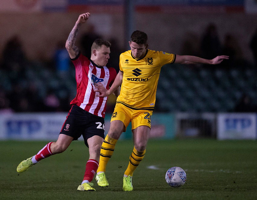 Lincoln City's Harry Anderson vies for possession with Milton Keynes Dons' Jordan Houghton<br /> <br /> Photographer Andrew Vaughan/CameraSport<br /> <br /> The EFL Sky Bet League One - Lincoln City v Milton Keynes Dons - Tuesday 11th February 2020 - LNER Stadium - Lincoln<br /> <br /> World Copyright © 2020 CameraSport. All rights reserved. 43 Linden Ave. Countesthorpe. Leicester. England. LE8 5PG - Tel: +44 (0) 116 277 4147 - admin@camerasport.com - www.camerasport.com