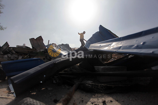 "Palestinians inspect the rubble of a training camp used by Hamas after it was hit by an Israeli missile strike in Gaza City, early Thursday, June 19, 2014. The Israeli military said five rockets were fired from Hamas-controlled Gaza into Israel. One rocket struck a house in southern Israel, causing damage but no injuries. Early Thursday, Israel responded with a series of airstrikes on ""terror activity"" sites in Gaza. It said ""direct hits"" were confirmed. There were no immediate reports of injuries. Photo by Ashraf Amra"