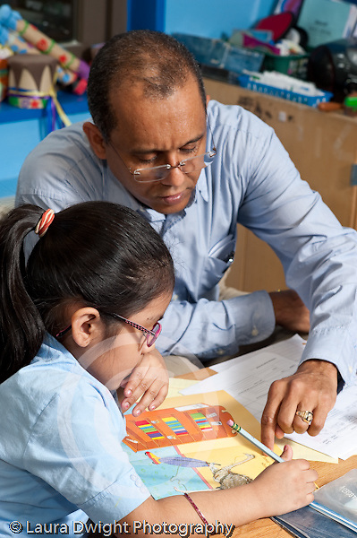 Afterschool Program homework help for children in primary grades male teacher working with girl