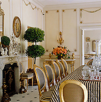 A set of black and white striped Louis XVI style dining chairs dominates this dining room which features hand-painted trompe l'oeil wall panels