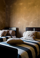 This twin bedroom has walls painted a yellow ochre and black and white striped bed covers