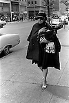 Manhattan street scene older fashionable dressed  woman carries a Union Jack flag hand bag as she hurries to an appointment. 1969