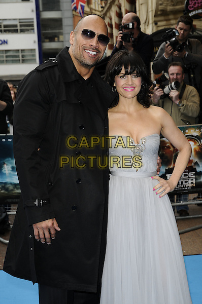 "DWAYNE ""THE ROCK"" JOHNSON & CARLA GUGINO.The UK film premiere of ""Race To Witch Mountain"" at Odeon Cinema West End, London, England..April 5th 2009.half 3/4 length black jacket trousers sunglasses shades strapless blue silver pale grey gray dress hand on hip  cleavage.CAP/CAN.©Can Nguyen/Capital Pictures."