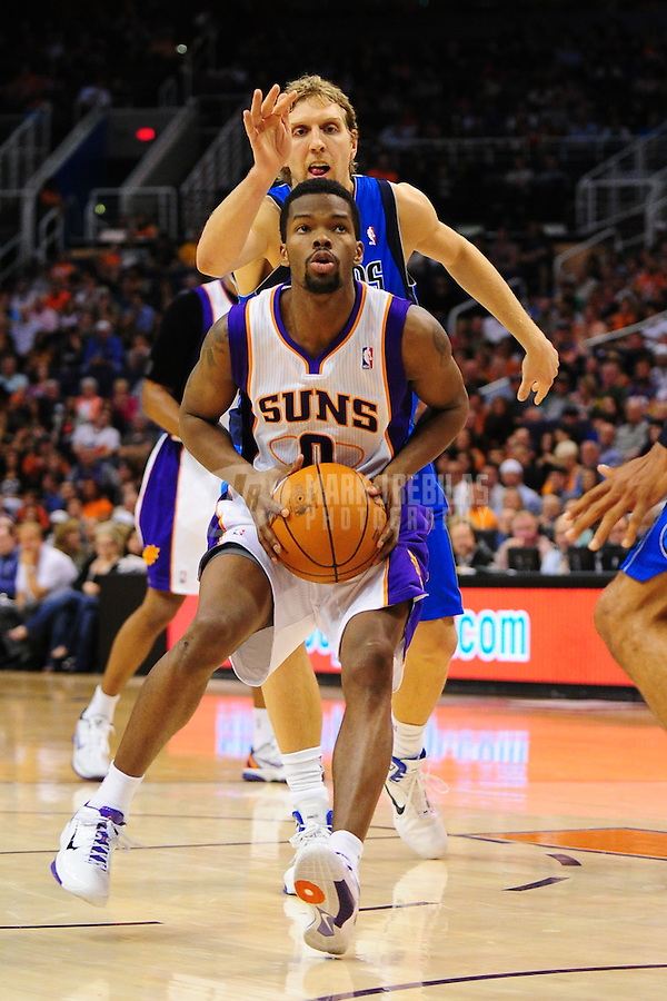 Mar. 27, 2011; Phoenix, AZ, USA; Phoenix Suns guard (0) Aaron Brooks drives to the basket against Dallas Mavericks forward (41) Dirk Nowitzki at the US Airways Center. The Maverick defeated the Suns 91-83. Mandatory Credit: Mark J. Rebilas-