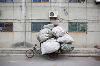 A bike overloaded with bags of recyclable materias stands parked next to an apartment building in Xian, Shaanxi, China.