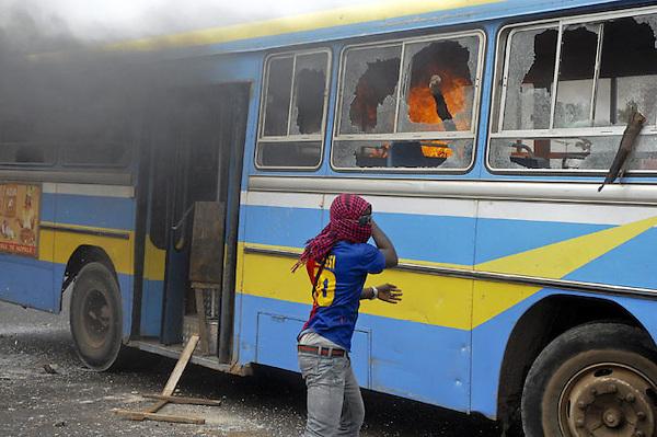 XNB03 DAKAR (SENEGAL), 1/2/2012.- Un manifestante lanza una piedra a un autobús en llamas durante los disturbios registrados en Dakar, Senegal, hoy, miércoles 1 de febrero de 2012. El Gobierno de Senegal condenó hoy los actos violentos ocurridos en la manifestación convocada ayer en Dakar por el Movimiento del 23 de junio (M23) contra la candidatura a los comicios presidenciales del presidente Abulaye Wade, que terminaron con la muerte de una persona, según la versión oficial. EFE/Aliou Mbaye