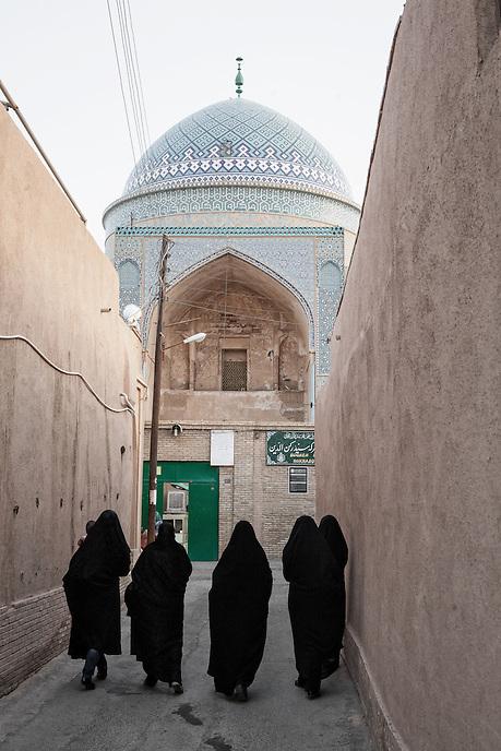 A group of Iranian women walk to the Bogheh-ye Sayyed Roknaddin in Yazd.