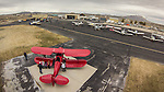 Open House at the WInnemucca Airport as photographed using the DJI Phantom quadcopter drone and GoPro Hero 3 camera from above the event. <br /> <br /> Aircraft on the ramp&ndash;red Waco  UPF-7 biplane was a trainer originally built in the late 1930s just prior to WWII