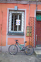 Modern hi-tech bicycle parked under a barred shop window.  Tomaszow Mazowiecki Central Poland