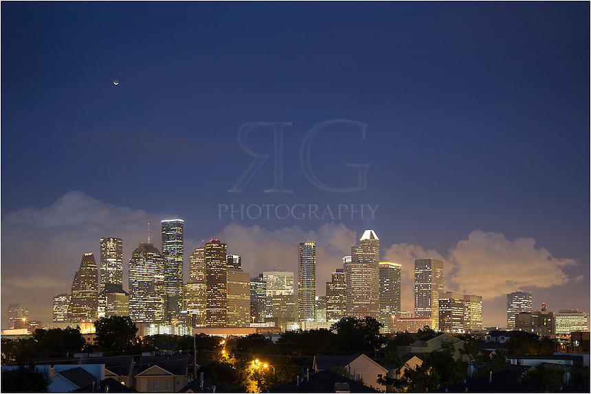 The crescent moon hangs over downtown Houston as storm clouds roll in the distance. This skyline image was captured from just west of the city. The tallest building in Houston, and also in Texas, is featured in this image - the JP Morgan Chase Tower - and rises 75 stories above the ground.