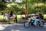 A boy and his horse watch a motorcyclist pass, in Jayuya, Puerto Rico, on Sunday, November 16, 2008. Many Puerto Ricans ride horses as a means of transportation in the mountain region.