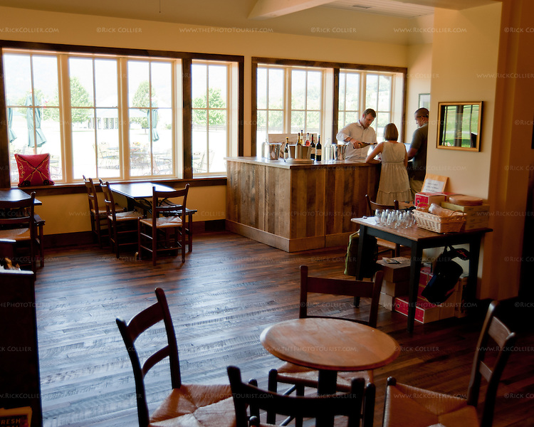 The tasting room at King Family Vineyards has two tasting bar areas and a number of comfortable seating areas throughout a large, rustic-styled room with a view of fields, polo grounds, and stables outside.
