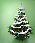 Decorated Christmas tree isolated on light green background