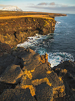 Golden hour along the Londrangar basalt cliffs in Hellissandur along Iceland's rugged coastline.