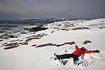 Women making a snow angel in the snow at Schoodic Point in Acadia National Park in Maine, USA