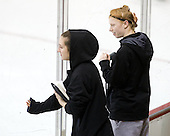 Brittany Esposito (NU - 7) and Kelly Wallace (NU - 5) watch their teammates warmup. - The Boston College Eagles defeated the visiting Northeastern University Huskies 2-1 on Sunday, January 30, 2011, at Conte Forum in Chestnut Hill, Massachusetts.