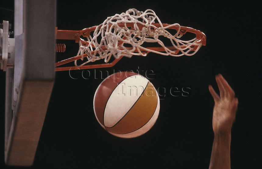 Basketball player shooting a ball through the net