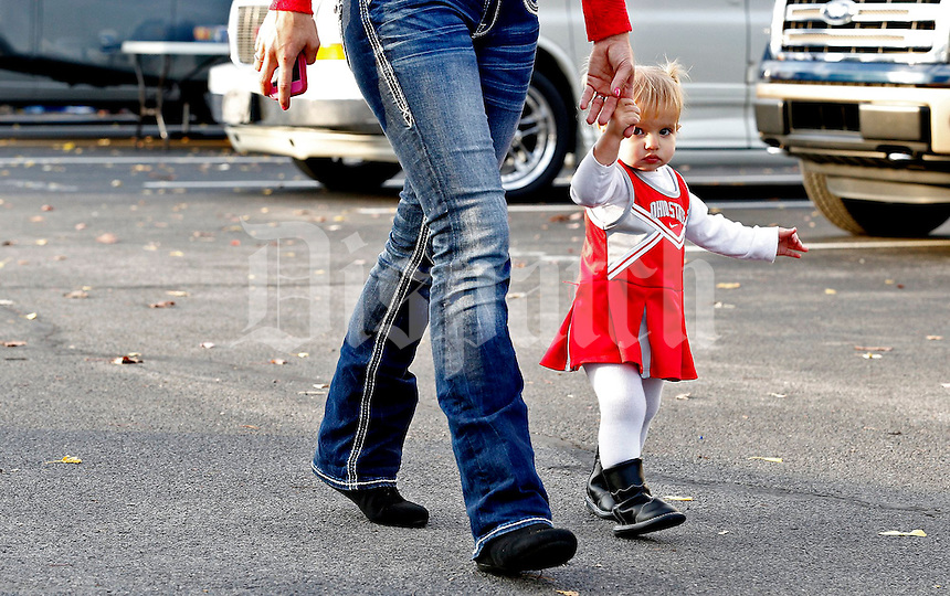 Mikayla Boyer, 2, holds her mother Jessica Boyer's hand while walking through the tailgate area before the first quarter of their game at Beaver Stadium in State College, PA on October 25, 2014. (Columbus Dispatch photo by Brooke LaValley)