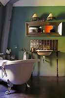 """In the bathroom of the """"Chatte Botte"""" the splashback behind the wash basin is lined with iridescent tiles and lit from above by two wall lights with fringed shades"""