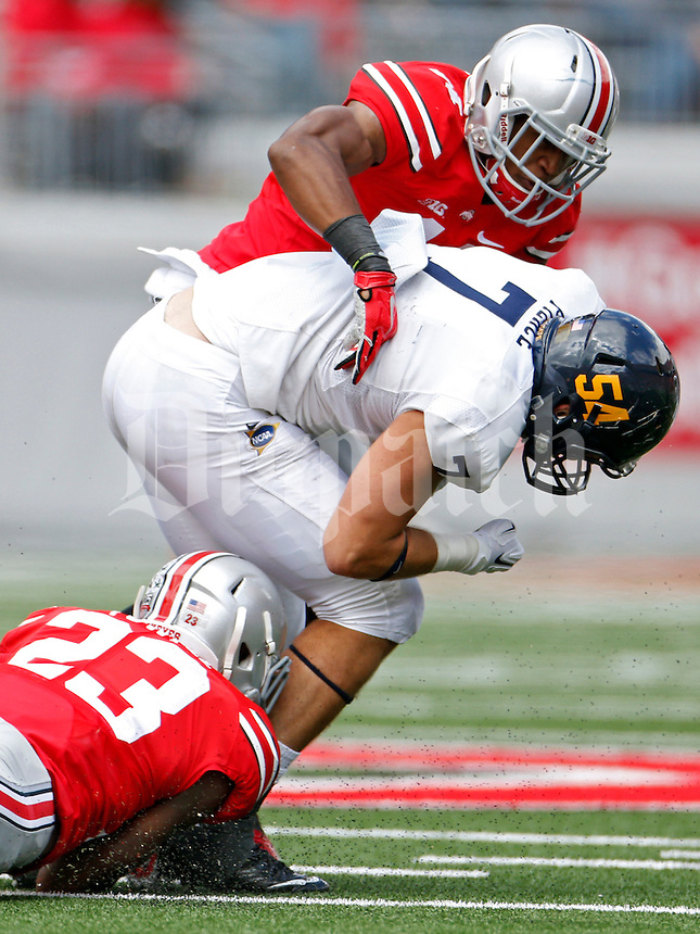 Ohio State Buckeyes safety Tyvis Powell (23) and Ohio State Buckeyes defensive back Vonn Bell (11) take down Kent State Golden Flashes tight end Casey Pierce (7) in the 2nd quarter of their game in Ohio Stadium on September 13, 2014.  (Dispatch photo by Kyle Robertson)