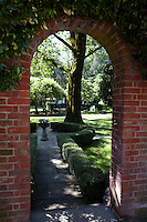 A glimpse through an archway in the red brick wall surrounding the garden