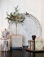 An olive tree, silver cutlery in a glass jar, vintage tins and Moroccan tray make a pretty display in the kitchen