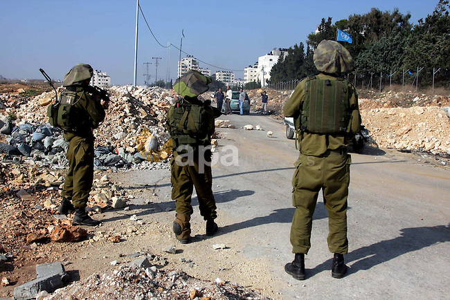 "An Israeli soldier walks along the controversial Israeli barrier after a protest in the Qalandia refugee camp, near the West Bank city of Ramallah, on November 9, 2009 to mark the 20th anniversary of the fall of the Berlin Wall in Germany. Palestinians are using the anniversary of the end of the Berlin wall to press their campaign against Israel's ""wall"", mostly a razor-wire fence interspersed with concrete barricades which Israel began building around the West Bank in 2002. The Jewish state has come under international censure for the barrier's de facto annexation of occupied West Bank land.. Photo by Issam Rimawi"