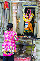 Woman Praying at Shrine to Hindu Goddess Durga, Sri Maha Mariamman Temple, George Town, Penang, Malaysia.