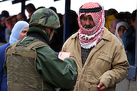 An Israeli soldier checks the ID card of a Palestinian man at the Hawara checkpoint in Nablus, West Bank, November 05, 2006. The Hawara checkpoint on the southern entrance of Nablus controls the movement of Palestinians between Nablus and the Southern part of the West Bank. The checkpoint, run by IDF paratroopers, doesn't limit with Israel. Photo by Quique Kierszenbaum