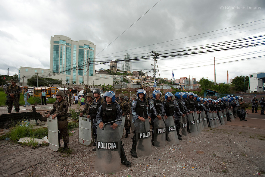 3 July 2009 - Tegucigalpa, Honduras  Honduran Police stand guard as supporters of Honduras' ousted President Manuel Zelaya pass by during a march near the presidential palace in Tegucigalpa. Zelaya has been forced into exile after being arrested by a group of soldiers in an apparent military coup. Photo credit: Benedicte Desrus