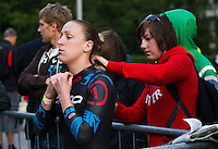 30 JUN 2011 - LONDON, GBR - Jodie Stimpson receives help zipping up her wetsuit before the start of the women's super sprint final at the GE Canary Wharf Triathlon (PHOTO (C) NIGEL FARROW)