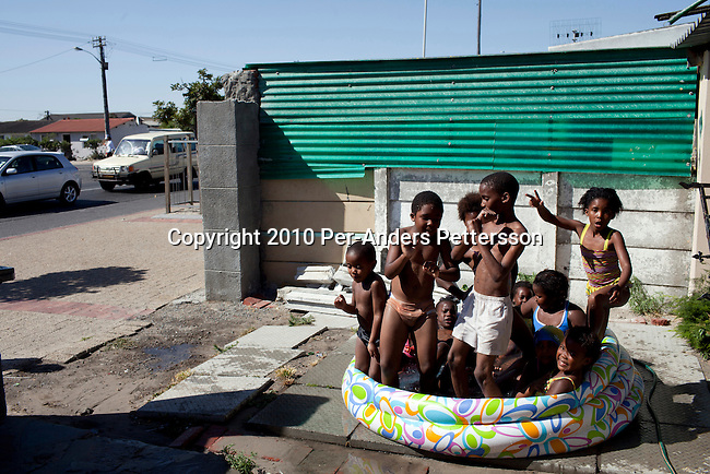 GUGULETU, SOUTH AFRICA - DECEMBER 14: Unidentified children cool themselves in a kids pool in a driveway on December 14, 2010, In Guguletu, a township outside Cape Town, South Africa. Guguletu is one of the biggest black townships in Cape Town and it was here where where British honeymooners Anni Dewani, 28, and Shrien Dewani, 31, were attacked. Anni Dewani was found with bullets in her chest in the back of the taxi after the newly weds were ambushed whilst traveling near a notorious settlement known as Barcelona. (Photo by Per-Anders Pettersson/Getty Images)