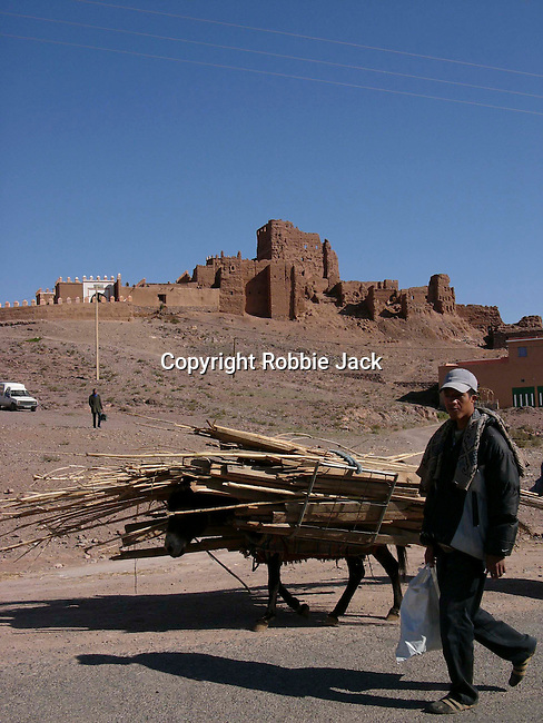Young Moroccan man with laden donkey in front of a kasbah near Quarzazate in Morocco.