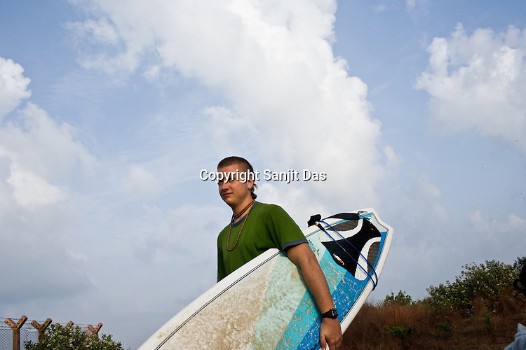 """Gaura Gopala, one of the devotees gets ready for the a surfing session on the Arabian Sea in Mangalore beach, Karnataka, India.  ..Krishna devotees in the Gaudiya Vaishnava tradition of Hinduism, they are known collectively as the """"surfing swamis."""" The """"surfing ashram"""" is growing in popularity and surfing here is a form of meditation, a spiritual practice leading to heightened states of awareness."""