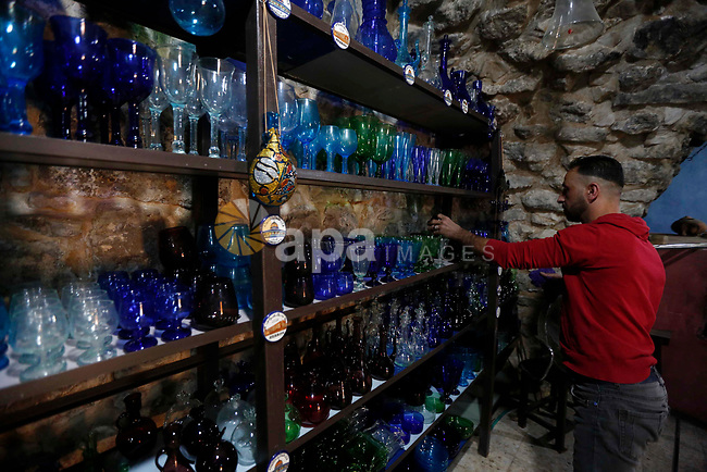 A Palestinian man inspects a piece of glass at a glassblowing  workshop near the Ibrahimi Mosque, in the West Bank city of Hebron. A glassblower or designer is responsible for designing, producing, decorating and finishing pieces of glass including, architectural glass, exhibition pieces, giftware, mirrors, stained, glass, windows and tableware. Photo by Wisam Hashlamoun