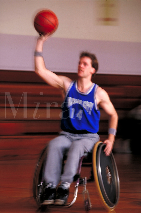 Wheelchair athlete playing indoor basketball; motion, blur, blurred, man, men, male, disabilities; MR#999; restrictions may be waived--contact photographer.