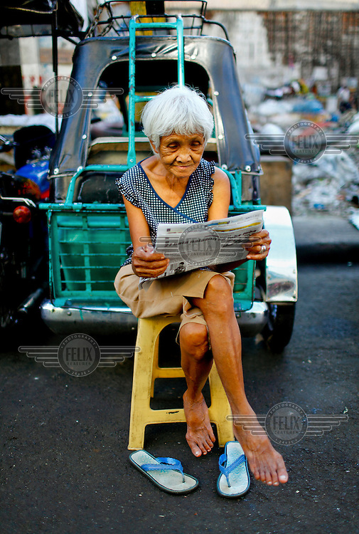 An elderly woman reads a newspaper while perched on a plastic stool in a car park.