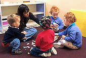 MR/Schenectady, New York.Schenectady Day Nursery; private, nonprofit day care center  in urban area..Teacher and students in toddler class do language arts lesson as they talk about shells. (Students aged 18-30 months, including twins; teacher is Chinese-American and Caucasian.) .MR: SDN-8.FC#: 22148-00515.©Ellen B. Senisi