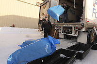 February 16, 2013  Race Manager and Marshal Mark Nordman unloads bales of straw from a van at the Willow airport to be flown flown to the 4 checkpoints on the east side the Alaska Range as chief pilot Bert Hanson looks on. ..Photo Copyright Jeff Schultz  -- Do not reproduce without written permission