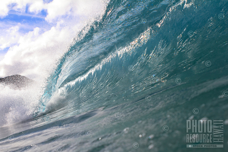 Clean breaking wave with morning light at Makua Beach, O'ahu.