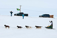 The first ever Jamaican musher, Newton Marshall, runs on the Bering Sea as trucks in the distance fly the Jamaican flag as he nears Nome during the 2010 Iditarod