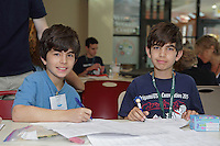 OrigamiUSA 2016 Convention at St. John's University, Queens, New York, USA. Nathan Joseph, Virginia (l) and Jack Joseph (r) check out the list of origami classes.