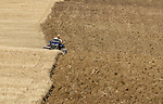 Farmer ploughing a field of recently cut crops
