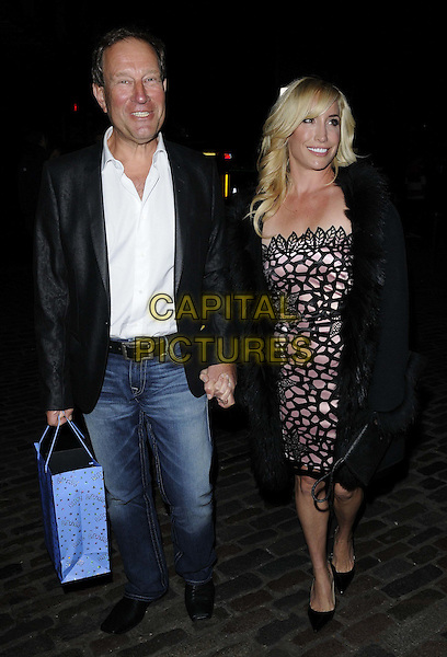 Richard Desmond & Janet Desmond.Sid Owen's 40th birthday party, Gilgamesh bar & restaurant, The Stable Market, Chalk Farm Rd., London, England..January 12th, 2012.full length black jacket white shit jeans denim pink dress pattern married holding hands husband wife .CAP/CAN.©Can Nguyen/Capital Pictures.