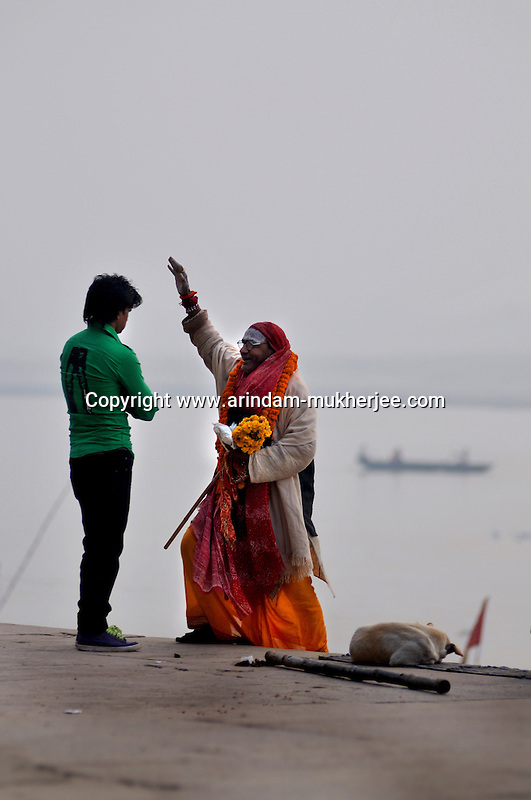A holy man blesses an Indian man at a ghat in Varanasi, Uttar Pradesh, India.