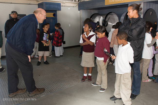 Oakland CA Senior volunteer at Chabot Space and Science Center answering question of second grade student on school field trip